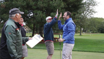 Golfers high fiving on the green