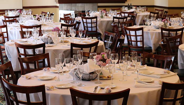 Seating arrangement in Deerfield Golf Club's banquet area. Large round tables are moderately spaced and prepared for formal dining