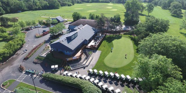 Deerfield Golf Club aerial view. A collection of golf carts sits in front of a large building with a wooden deck and an adjacent small practice area